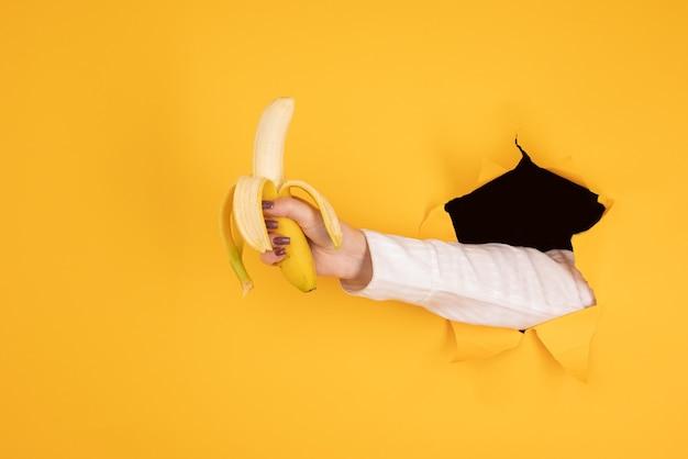 Kobieca ręka trzymająca owoc bananowy, koncepcja odżywiania, ludzka ręka trzymająca banana w otworze pomarańczowym tle