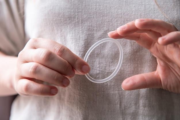 Kobieca ręka trzymająca pierścień antykoncepcyjny, pierścień dopochwowy do zbliżenia antykoncepcji