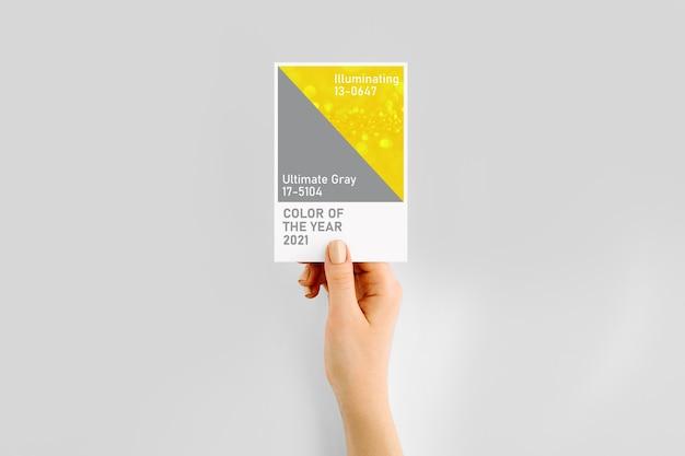 Kobieca ręka trzymająca próbki kolory roku 2021- ultimate grey and illuminating