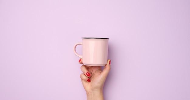 Kobieca ręka trzymająca różowy ceramiczny kubek na fioletowym tle, przerwa i picie kawy, baner