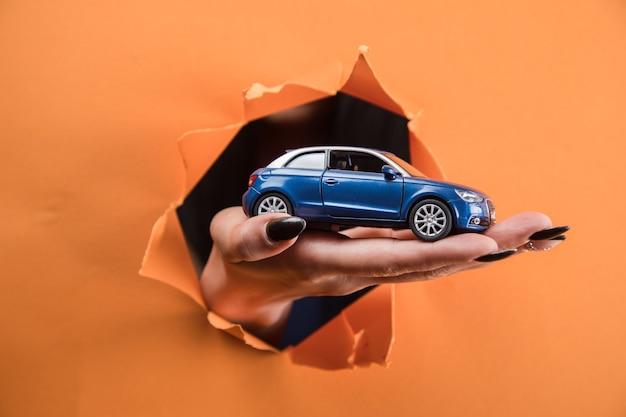 Kobieca ręka trzymająca samochodzik na pomarańczowym tle