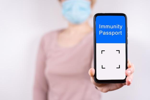 Kobieca ręka trzymająca telefon komórkowy z cyfrowym paszportem odpornościowym