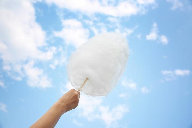 Kobieca ręka trzymająca watę cukrową na niebieskim niebie