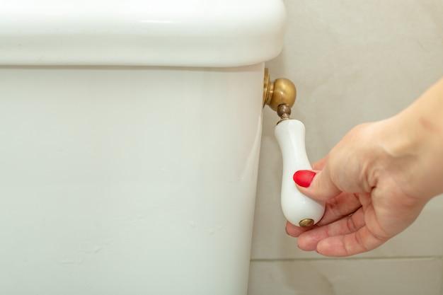 Kobieca ręka w dół uchwytu toalety