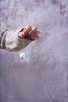 Kobieca ręka w przytulnym różowym swetrze trzyma dzwonek. koncepcja dekoracji świątecznej