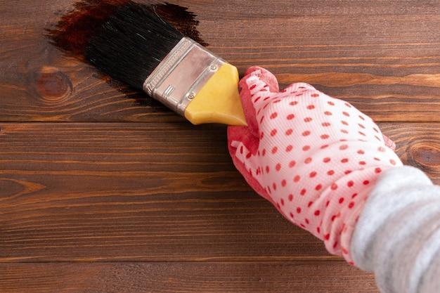 Kobieca ręka w rękawiczce maluje pędzlem drewnianą ścianę
