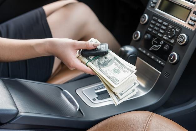 Kobieca ręka w samochodzie oferująca klucze i dolary