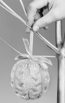 Kobieca ręka wisząca przytulna, dzianinowa piłka świąteczna diy do alternatywnej choinki z suchego drewna pomalowanego na kolor srebrny. kreatywny czarno-biały minimalny pionowy obraz bożego narodzenia. minimalna koncepcja hygge.