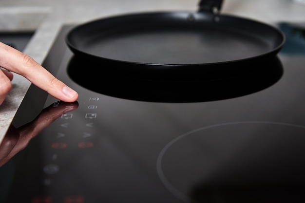 Kobieca ręka włącza nowoczesną kuchenkę indukcyjną w kuchni
