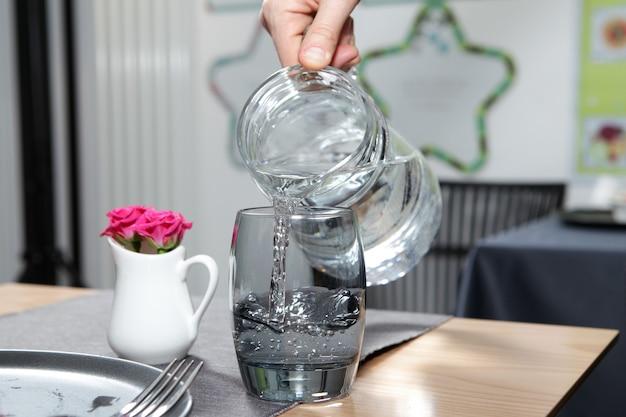 Kobieca ręka wlewa przezroczystą wodę z dzbanka do ciemnej szklanki. zbliżenie.