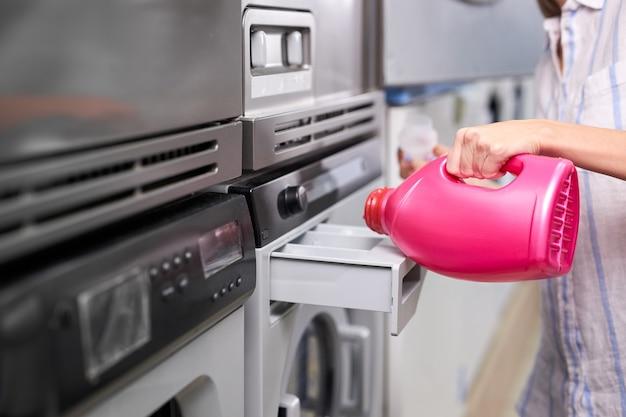 Kobieca ręka wlewa tłusty detergent z różowej butelki do komory pralki w pralni