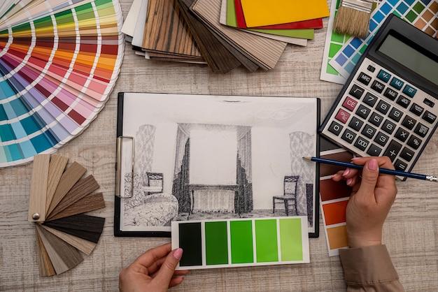 Kobieca ręka wybiera kolor z palety na planie architektonicznym, koncepcja renowacji
