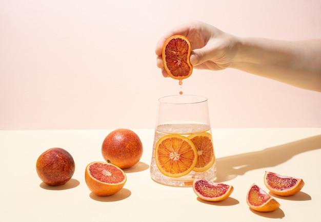 Kobieca ręka wyciskająca połowę dojrzałej soczystej krwistej pomarańczy do szklanki wody użytkowej z plasterkami cytrusów na żółto-różowym kolorze