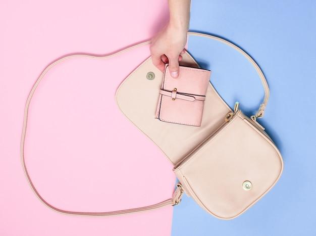 Kobieca ręka wyjmuje skórzany portfel z torebki na pastelowym tle