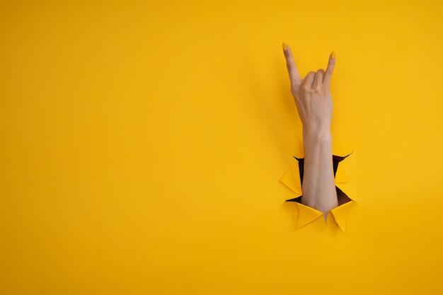 Kobieca ręka wykonująca gest rock and rolla, impreza, koza na żółtym tle