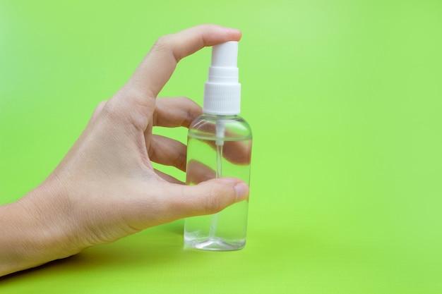 Kobieca ręka z antyseptykiem na zielonym tle z bliska. pojęcie higieny i czystości. środek dezynfekujący