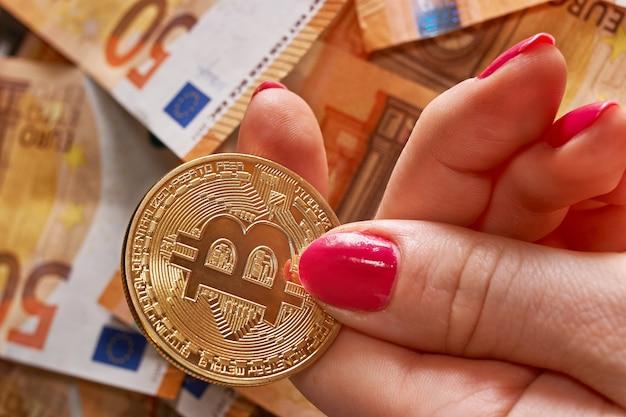 Kobieca ręka z bitcoinem i 50 pięćdziesiąt euro banknotów w tle