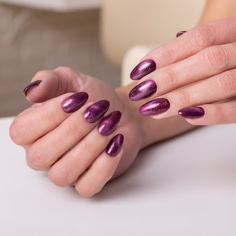 Kobieca ręka z bordowymi paznokciami do manicure