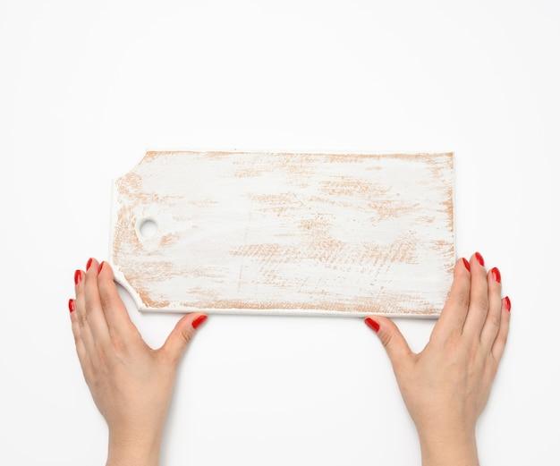 Kobieca ręka z czerwonym manicure trzyma pustą białą drewnianą prostokątną deskę do krojenia w kuchni