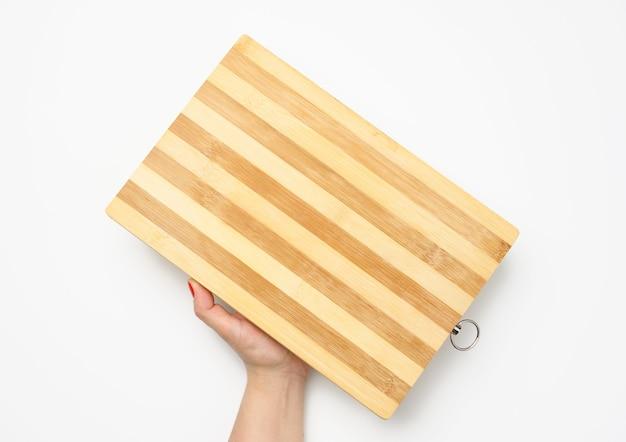 Kobieca ręka z czerwonym manicure trzyma pustą drewnianą prostokątną kuchnię do krojenia na białym tle