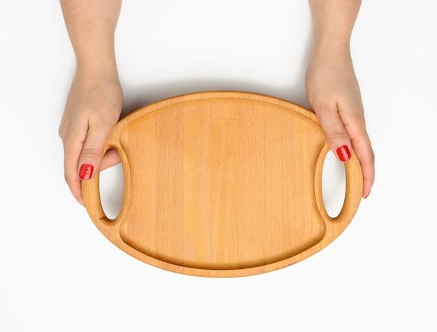 Kobieca ręka z czerwonym manicure trzyma pustą okrągłą deskę do krojenia kuchni na białym tle