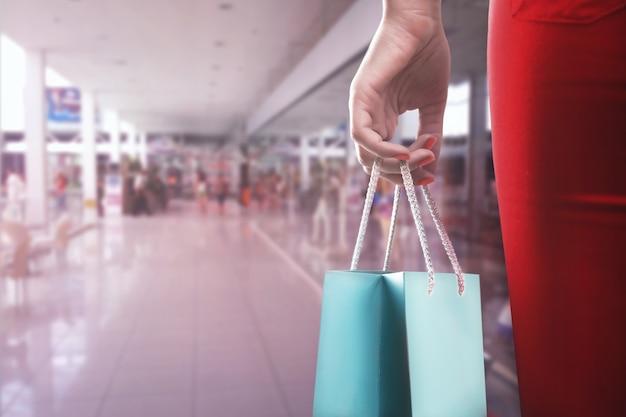 Kobieca ręka z dwiema torbami na zakupy w centrum handlowym