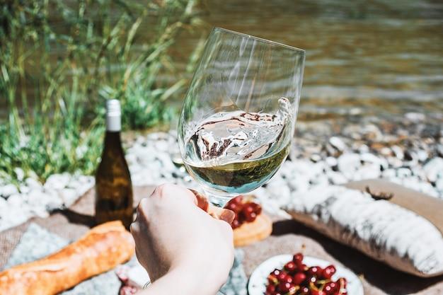Kobieca ręka z kieliszkiem białego wina na wybrzeżu rzeki i piknikowym tle