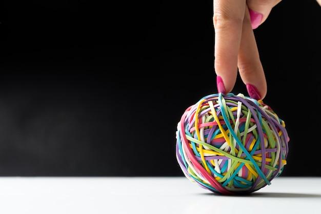 Kobieca ręka z kolorowymi gumowymi piłkami