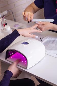 Kobieca ręka z paznokciami do manicure w lampie żelowej w salonie kosmetycznym