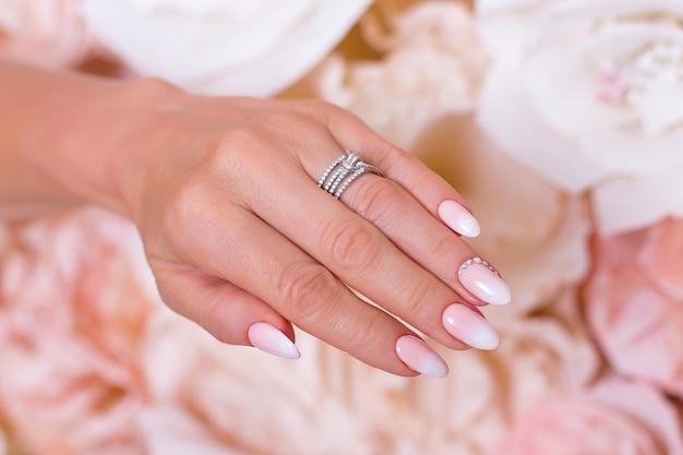 Kobieca ręka z paznokciami ombre manicure różowy lakier hybrydowy na tle kwiatów papieru