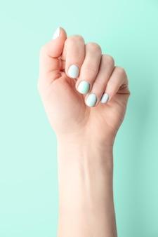Kobieca ręka z zadbanymi i pomalowanymi paznokciami na zielonym tle