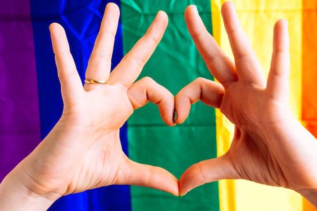 Kobieca ręka z zielonymi pomalowanymi paznokciami tworząca serce z flagą lgbtq w tle. koncepcja miłości do homoseksualistów. tolerancja