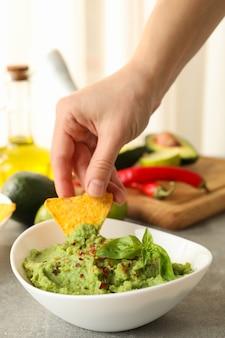 Kobieca ręka zanurza kawałek chipsów w guacamole