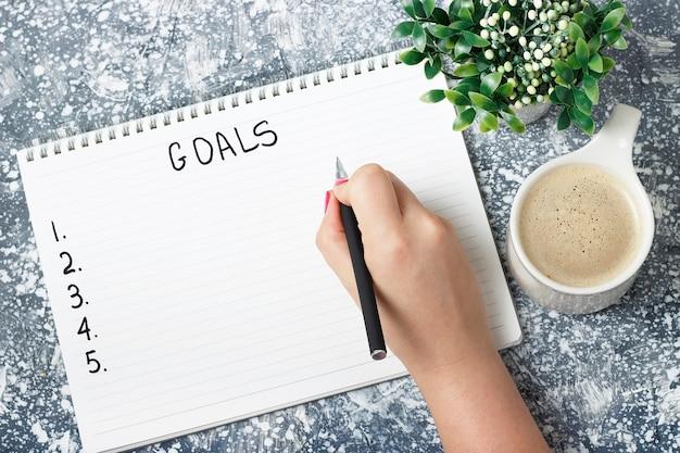 Kobieca ręka zapisuje cele w zeszycie, koncepcję planowania