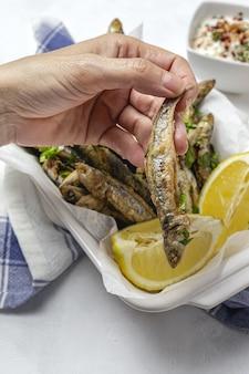 Kobieca ręka ze smażonymi anchois z cytryną i natką pietruszki. koncepcja owoce morza