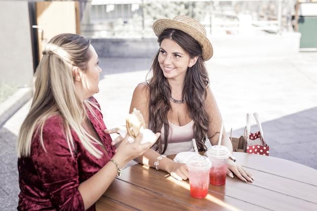 Kobieca rozmowa. ładna pulchna kobieta rozmawia ze swoim najlepszym przyjacielem, trzymając hamburgera