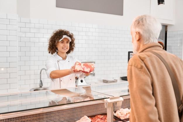 Kobieca rzeźnik demonstruje mięso starszemu mężczyźnie.