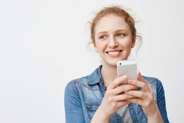 Kobieca śliczna rudowłosa dziewczyna z niechlujną fryzurą, patrząc na bok i uśmiechając się szeroko, trzymając smartfon