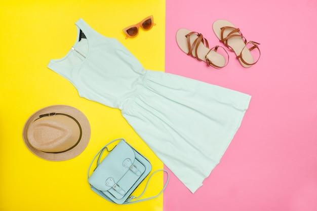 Kobieca szafa. miętowa sukienka, torebka, buty i czapka. jasne różowo-żółte tło. koncepcja mody