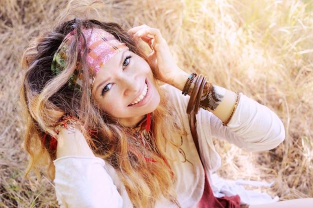 Kobieca szyja i uszy z naszyjnikiem boho i kolczykami z czerwonymi piórami i brązową skórą, ręcznie robiona biżuteria