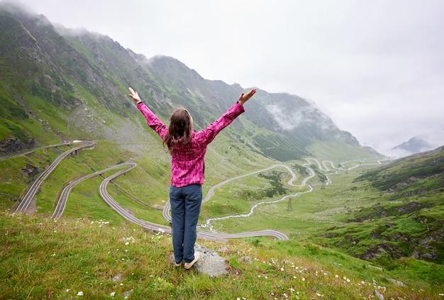 Kobieca turystyczna pozycja z jej rękami szeroko otwarty i patrzeje w górę. widok z tyłu