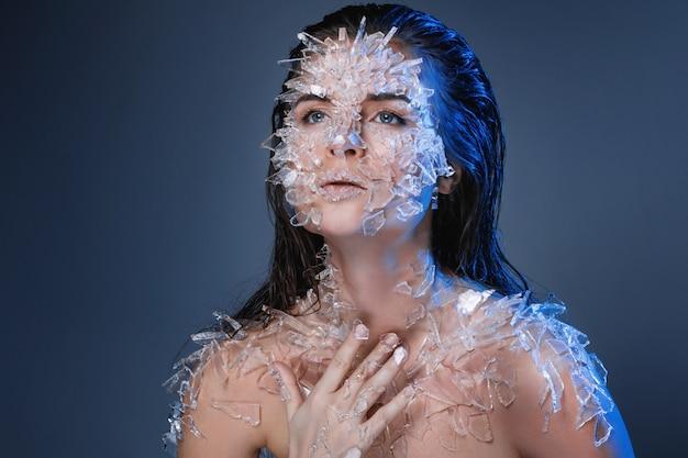Kobieca twarz pokryta dużą ilością małych kawałków szkła