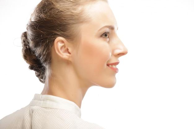 Kobieca twarz w profilu z makijażem i fryzurą