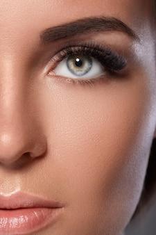 Kobieca twarz z pięknymi brwiami i sztucznymi rzęsami