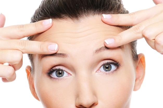 Kobieca twarz ze zmarszczkami na czole