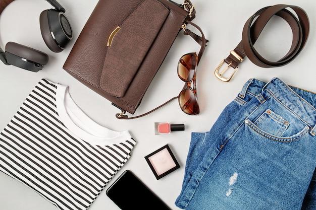 Kobiece akcesoria mody, dżinsy, okulary przeciwsłoneczne, smartfon, słuchawki i torebka