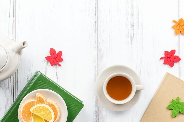 Kobiece biurko do pracy leżało płasko z pamiętnikiem, okularami, książką, kubkiem do herbaty, słodyczami i filcowym wystrojem.