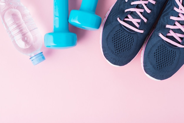 Kobiece buty sportowe, niebieskie hantle i butelka wody na różowym tle