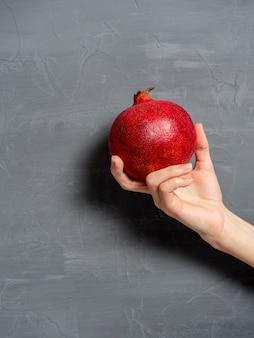 Kobiece dłoń trzyma dojrzały, soczysty owoc granatu w całości na szarym tle. owoce zdrowe i smaczne. zdjęcie pionowe