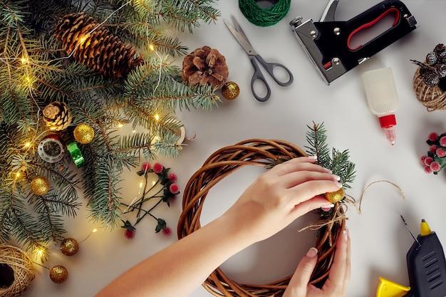 Kobiece dłonie dekorują świąteczny wieniec świerkowymi gałązkami z czerwoną jagodą i leśnymi szyszkami. białe tło. koncepcja noworoczna.
